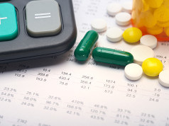 Sheet of paper with calculator and medicine pills on top