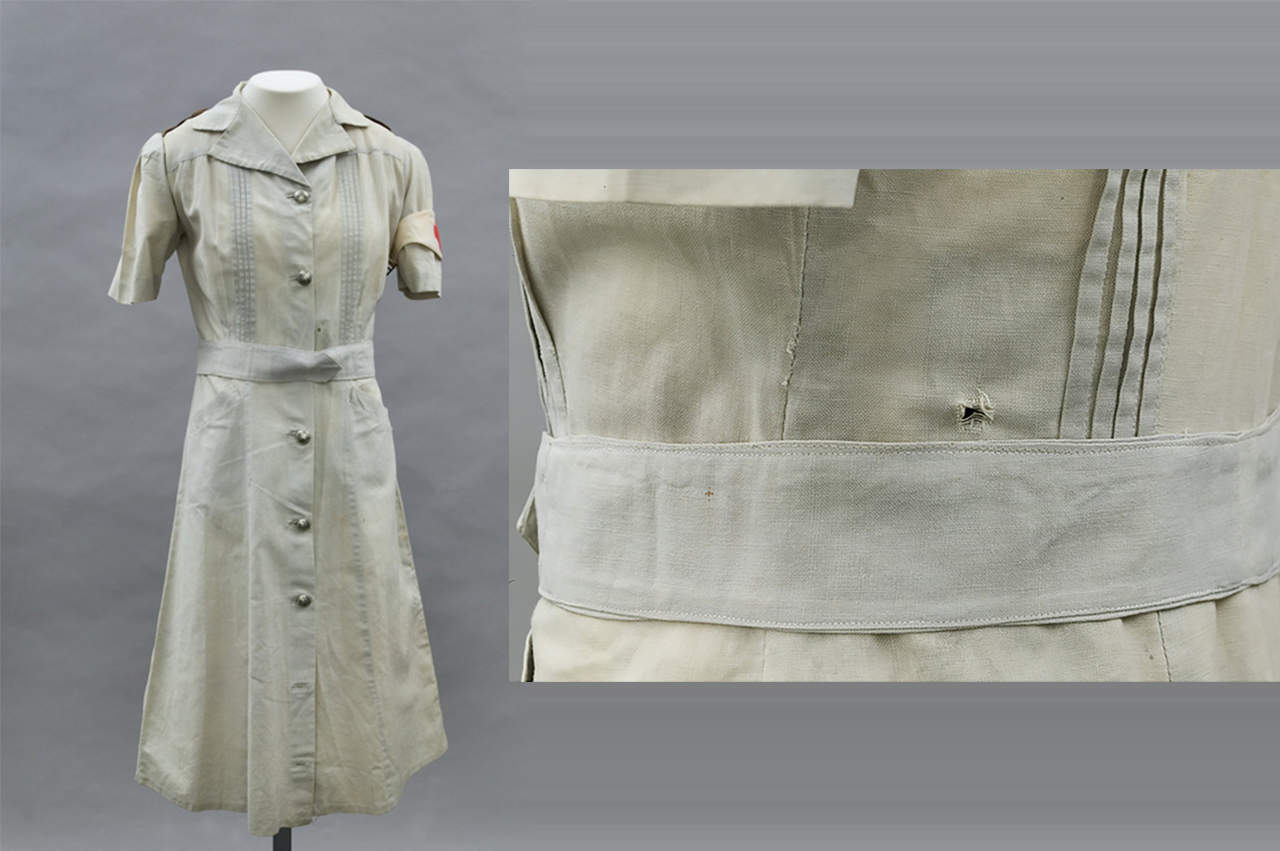 Uniform worn by Bullwinkel when she survived being shot. A bullet entry hole can be seen in the left side of the back bodice, the exit hole is located 35mm above the waist seam at the left center front.