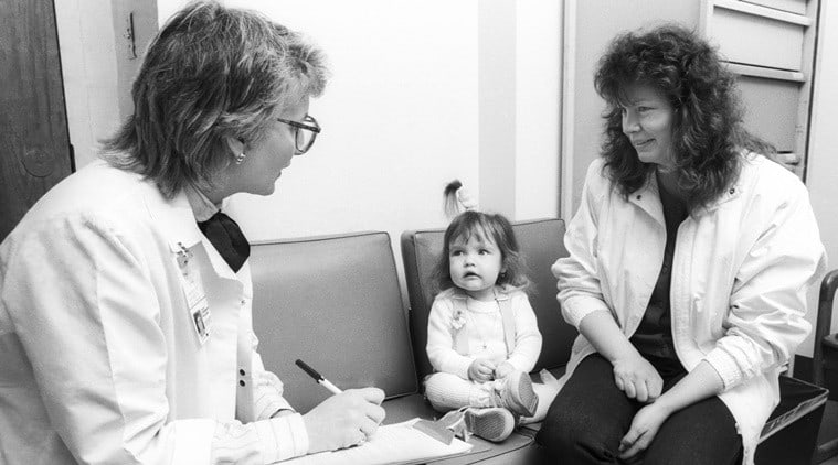 In this June 1988 photo provided by Children's Hospital of Wisconsin, Nicole Frye, center, looks up at Lynn Bartos, pediatric nurse for Children's Hospital of Wisconsin Gastroenterology Clinic, left, at Children's Hospital of Wisconsin in Wauwatosa, Wis. The nurse and family were featured on the cover of the hospital's nursing magazine in 1988 for a story about long term care. Bartos and Nicole Krahn, once Frye, recently reunited after about 25 years, with Krahn now taking care of Bartos who has rheumatoid arthritis. (Jeff Surges/Children's Hospital of Wisconsin via AP)