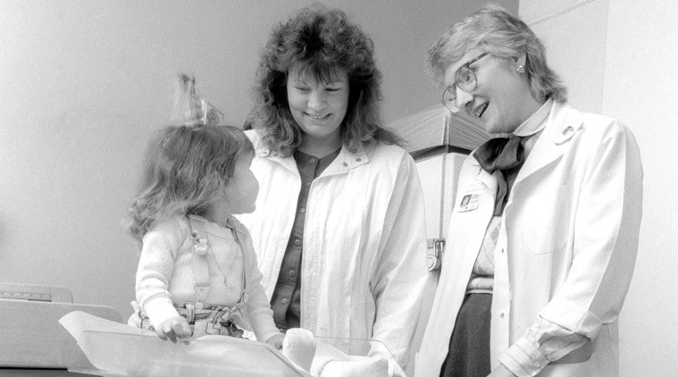 In this June 1988 photo provided by Children's Hospital of Wisconsin, Lynn Bartos, right, and Rose Frye weigh Nicole Frye, left, at Children's Hospital of Wisconsin in Wauwatosa, Wis. The nurse and family were featured on the cover of the hospital's nursing magazine in 1988 for a story about long term care. Bartos and Nicole Krahn, once Frye, recently reunited after about 25 years, with Krahn now taking care of Bartos who has rheumatoid arthritis. (Jeff Surges/Children's Hospital of Wisconsin via AP)