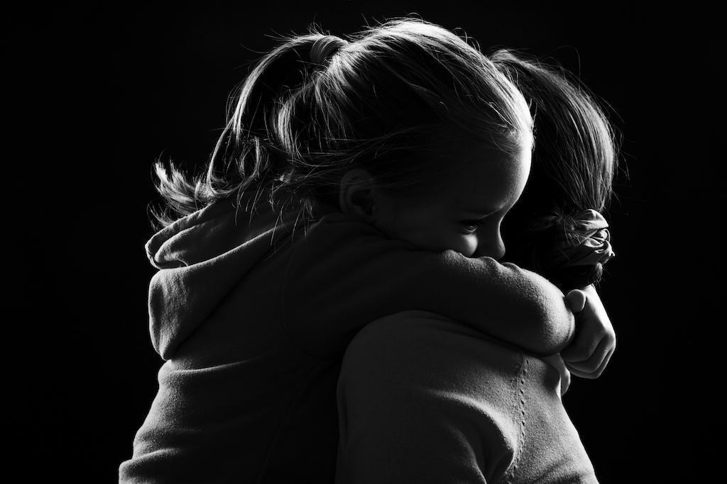 Little girl hugs her mother