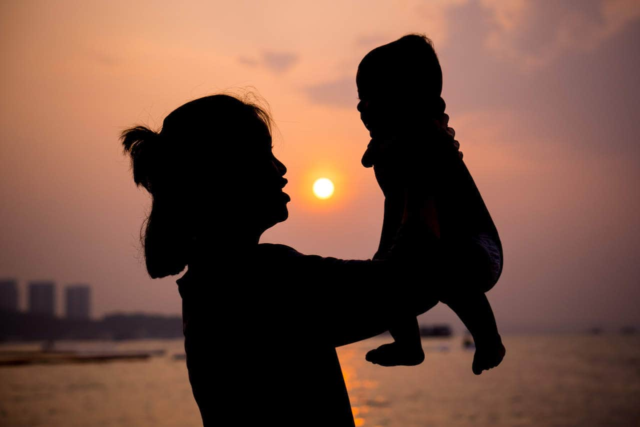 Silhouette Of Mother Plays With Her Toddler Against The Sunset.