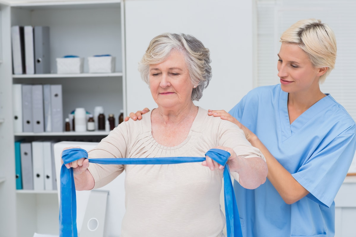 Nurse helping senior patient in exercising with resistance band in clinic